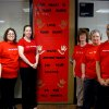 "Several members of the Rose State College admissions staff stand in front of their decorated door promoting ""Go Red for Women,"" during February Heart Month. Community Photo By: Steve Reeves Submitted By: Donna, Choctaw"