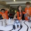 Photo - In this Aug. 14, 2013, photo, Saci Marty, 10, center, and Callum Brown, 11, at right, put their robotic Lego Mindstorms units through an obstacle course during a Digital Media Academy workshop, in Stanford, Calif. Lego's new Mindstorms sets rolling out next month are keenly anticipated by Silicon Valley engineers_many of whom were drawn to the tech sector by the flagship kits that came on the market in 1998, introducing computerized movement to the traditional snap-together toy blocks and allowing the young innovators to build their first robots. (AP Photo/Marcio Jose Sanchez)