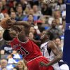 Photo - Chicago Bulls guard Jimmy Butler (21) is fouled by Dallas Mavericks center Samuel Dalembert (1), of Haiti, during the first half of an NBA basketball game on Friday, Feb. 28, 2014, in Dallas. (AP Photo/John F. Rhodes)