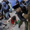 A member of the punk group Pussy Riot lies on the ground as the group are attacked by Cossack militia in Sochi, Russia, on Wednesday, Feb. 19, 2014. The group had gathered to perform in a downtown Sochi restaurant, about 30km (21miles) from where the Winter Olympics are being held.They left the restaurant wearing bright dresses and ski masks and had only been performing for a few seconds when they were set upon by Cossacks. (AP Photo/Morry Gash)