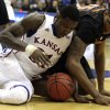 Kansas forward Jamari Traylor, left, and Texas center Cameron Ridley battle for a loose ball during the first half of an NCAA college basketball game on Saturday, Feb. 16, 2013, in Lawrence, Kan. (AP Photo/Ed Zurga)