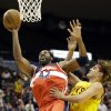 Photo - Washington Wizards center Nene (42), of Brazil, shoots against Cleveland Cavaliers forward Anderson Varejao, also of Brazil, in the first half of an NBA preseason basketball game on Wednesday, Oct. 23, 2013, in Cincinnati. (AP Photo/Al Behrman)