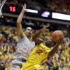 Photo - Iowa State forward Dustin Hogue, right, drives to the basket in front of Kansas forward Perry Ellis (34) during the first half of an NCAA college basketball game, Monday, Jan. 13, 2014, in Ames, Iowa. (AP Photo/Charlie Neibergall)