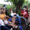 Photo -   In this April 22, 2012 photo, sisters Alit Astini, left, and Putu Restiti display Barbie dolls as they sit on wheel chair outside their house in Songan village, Kintamani, Bali, Indonesia. The disabled sisters were kept out of school and had no friends. But like children everywhere, they had powerful imaginations. After being given a Barbie doll, they started stitching tiny, intricate outfits for her from their mother's sewing scraps. And in doing so, they created a new world for themselves. (AP Photo/Firdia Lisnawati)