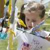 Six year old Lauren Hugo ties a ribbon onto a mass of other ribbons as a part of the