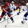Photo - Washington Capitals right wing Troy Brouwer (20) goes for the puck with Tampa Bay Lightning defenseman Eric Brewer (2) in the second period of an NHL hockey game on Sunday, April 13, 2014, in Washington. (AP Photo/Alex Brandon)