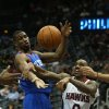 Photo - Atlanta Hawks guard Jeff Teague (0) loses control of the ball after he attempted a shot under the defense of Philadelphia 76ers forward Thaddeus Young (21) in the first half of an NBA basketball game Monday, March 31, 2014, in Atlanta. (AP Photo/Jason Getz)