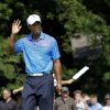 Photo -   Tiger Woods acknowledges the gallery after making birdie on the 11th hole during the first round of the BMW Championship PGA golf tournament at Crooked Stick Golf Club in Carmel, Ind., Thursday, Sept. 6, 2012. (AP Photo/Charles Rex Arbogast)