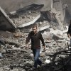 Palestinians walk through the debris after an Israeli air strike on building in Gaza City, Sunday, Nov. 18, 2012. The Israeli military widened its range of targets in the Gaza Strip on Sunday to include the media operations of the Palestinian territory\'s Hamas rulers, sending its aircraft to attack two buildings used by both Hamas and foreign media outlets. (AP Photo/Adel Hana)
