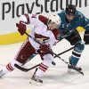 Photo - Phoenix Coyotes' Tim Kennedy (34) and San Jose Sharks' Jason Demers vie for the puck during the first period of an NHL preseason hockey game in San Jose, Calif., Saturday, Sept. 21, 2013. (AP Photo/Mathew Sumner)