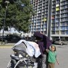 In this photo taken Tuesday, Sept. 24, 2013, a young Somali boy accompanies his mother who covers her head to avoid being photographed by the high rise where many Somali people live in Minneapolis. It\'s been six years since Minnesota first began furnishing young fighters to al-Shabab, the terror group that has claimed responsibility for the deadly mall attack in Kenya. (AP Photo/Jim Mone)