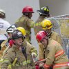 Firefighters remove a victim from the rubble after a section of a parking garage under construction at Miami-Dade College campus collapsed, Wednesday, Oct. 10, 2012 in Doral, Fla., killing one worker and trapping at least two others in the rubble, officials said. (AP Photo/J Pat Carter)