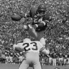 FOOTBALL: University of Oklahoma (OU) running back Joe Washington scores a touchdown by leaping over Utah State\'s Jim Boccia in this Sept 28, 1974 game in Norman. COPYRIGHT 1974 OKLAHOMA PUBLISHING COMPANY
