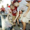 From right, siblings Braden Lutts, 15, Bryce Lutts, 12, and Rylee Lutts, 10, of Oklahoma City, check food on grills while cooking in the parking lot before the BCS National Championship college football game between the University of Oklahoma Sooners (OU) and the University of Florida Gators (UF) on Thursday, Jan. 8, 2009, at Dolphin Stadium in Miami Gardens, Fla. PHOTO BY NATE BILLINGS, THE OKLAHOMAN