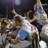 Oklahoma\'s Dusty Dishman, left, Kyle Hayes, center, and Craig Aikin, right, celebrate with teammates following an NCAA college baseball tournament regional game at English Field in Blacksburg, Va., Sunday, June 2, 2013. Oklahoma won 10-4. (AP Photo/Michael Shroyer) ORG XMIT: VAMS163