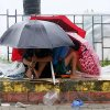 Residents huddle together under their umbrellas as strong winds and slight rain are brought by Typhoon Koppu Sunday, Oct. 18, 2015 in Manila, Philippines. The slow-moving typhoon blew ashore with fierce wind in the northeastern Philippines early Sunday, toppling trees and knocking out power and communications. Officials said there were no immediate reports of casualties. (AP Photo/Bullit Marquez)