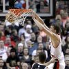 Photo - Portland Trail Blazers center Meyers Leonard, right, scores against Brooklyn Nets center Brook Lopez during the first quarter of an NBA basketball game in Portland, Ore., Wednesday, March 27, 2013. (AP Photo/Don Ryan)