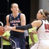 Photo - Connecticut's Breanna Stewart, left, looks for help from the defensive pressure of Louisville's Sara Hammond during the first half of an NCAA college basketball game, Monday, March 3, 2014, in Louisville, Ky. (AP Photo/Timothy D. Easley)
