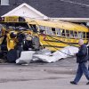 Residents walk past a school bus destroyed by tornado in Henryville, Ind., Sunday, March 4, 2012. Calm weather gave dazed residents of storm-wracked towns a respite on Sunday as they dug out from a chain of tornadoes that cut a swath of destruction from the Midwest to the Gulf of Mexico, killing at least 39 people. (AP Photo/Nam Y. Huh) ORG XMIT: INNH121