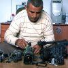 This undated publicity photo released by Kino Lorber, Inc. shows Co-director Emad Burnat with his five broken cameras. Burnat and Guy Davidi co-directed the documentary film,