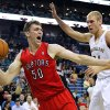 Photo - Toronto Raptors forward Tyler Hansbrough (50) drives against New Orleans Pelicans center Greg Stiemsma, right, during the first half of an NBA basketball game in New Orleans, Wednesday, March 19, 2014. (AP Photo/Jonathan Bachman)