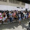 Residents line up for relief supplies at an evacuation center Thursday Dec. 6, 2012 after Typhoon Bopha hit New Bataan township, Compostela Valley in southern Philippines. The powerful typhoon that washed away emergency shelters, a military camp and possibly entire families in the southern Philippines has killed hundreds of people with nearly 400 missing, authorities said Thursday. (AP Photo/Bullit Marquez)