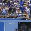 Fans try to catch a ball hit for a two-run home run hit by Colorado Rockies\' Michael Cuddyer as Los Angeles Dodgers right fielder Skip Schumaker (55) looks on during the fifth inning of a baseball game on Sunday, July 14, 2013, in Los Angeles. (AP Photo/Mark J. Terrill)