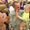 Aaron Ashworth, Tulsa, gives a high five to 20 month old son Stryker as his wife Rosie holds six-month-old Hunter as he and other soldiers from the 1-245th Airfield Operations Battalion return home on Tuesday, August 16, 2011, in Norman, Okla. after spending eight months in Afghanistan. Ashworth was home for 15 days to witness the birth of his youngest in February. Photo by Steve Sisney, The Oklahoman