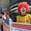 Photo - A protester dressed as Ronald McDonald participates in a rally to demand higher wages for fast-food workers outside a McDonald restaurant in Seoul, South Korea, Thursday, May 15, 2014. About 30 labor union members joined the global action to ask higher pay for part-time workers.(AP Photo/Ahn Young-joon)