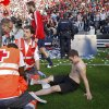 Photo - Osasuna's supporter lies on the pitch after one fence of the stadium was broken while people celebrated their team's, during their last  Spanish League soccer match between Osasuna and Betis,, at El Sadar stadium, in Pamplona northern Spain, Sunday, May 18, 2014. (AP Photo/STR)