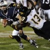 Photo - Connecticut quarterback Chandler Whitmer, left, is tackled by Towson's Greg Grant, back, and Towson's Telvion Clark, right, during the second half of an NCAA college football game at Rentschler Field in East Hartford, Conn., Thursday, Aug. 29, 2013. (AP Photo/Jessica Hill)
