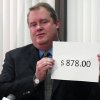 Photo -   Alaska Revenue Commissioner Bryan Butcher holds up the amount of this year's Permanent Fund Dividend during a news conference Tuesday, Sept. 18, 2012, in Anchorage, Alaska. Butcher announced this year's check from the state's oil riches will be $878 for nearly every single Alaskan. (AP Photo/Mark Thiessen)