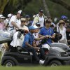 Photo - Tiger Woods, center, gets a ride in a cart with his caddy Joe LaCava, left, after play was suspended due to approaching inclement weather during the first round of the Cadillac Championship golf tournament, Thursday, March 6, 2014, in Doral, Fla. (AP Photo/Lynne Sladky)