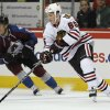 Chicago Blackhawks right wing Andrew Shaw, front, picks up a loose puck as Colorado Avalanche right wing PA Parenteau skates nearby during the third period of the Avalanche\'s 6-2 victory in an NHL hockey game in Denver on Friday, March 8, 2013. (AP Photo/David Zalubowski)