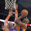 Photo -   Los Angeles Lakers guard Kobe Bryant, right, puts up a shot as Phoenix Suns center Marcin Gortat, of Poland, defends during the first half of their NBA basketball game, Friday, Nov. 16, 2012, in Los Angeles. (AP Photo/Mark J. Terrill)