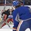 Photo - Canadian Olympic women's team goaltender Shannon Szabados defends against Edmonton Oilers Ryan Jones as she takes part in the Oilers NHL hockey practice in Edmonton, Alberta, Wednesday, March 5, 2014. (AP Photo/The Canadian Press, Jason Franson)