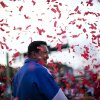 Under pouring confetti, Venezuela\'s President Hugo Chavez smiles during a campaign rally in Valencia, Venezuela, Wednesday, Oct. 3, 2012. Chavez is running for re-election against opposition candidate Henrique Capriles in presidential elections on Oct .7. (AP Photo/Rodrigo Abd)