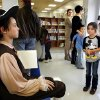 Ross Outhier, left, attracts the attention of a small girl as he sits briefly between talks about Thomas Paine, the figure he portrays. Wearing authentic era attire, students in Rhonda Watkins\' fourth and fifth grade social studies classes at Schwartz Elementary School portrayed various figures from the American Revolution period during a living history museum program in the school\'s library on Wednesday, Jan. 30, 2013. The students selected a historical person from a list provided by Watkins, and were required to research the subject, write a report and make a verbal presentation about the person. All students in the school were invited to the library to hear the characters tell about their lives. Photo by Jim Beckel, The Oklahoman