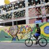 Photo - A cyclist makes his way down a street decorated with images celebrating the 2014 soccer World Cup in Fortaleza, Brazil, Monday, June 16, 2014.  (AP Photo/Marcio Jose Sanchez)