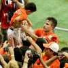 Photo - Netherlands' Robin van Persie holds a boy as he celebrates with fans after winning the World Cup quarterfinal soccer match between the Netherlands and Costa Rica at the Arena Fonte Nova in Salvador, Brazil, Saturday, July 5, 2014. Netherlands beat Costa Rica 4-3 on penalties to reach semifinals of the World Cup. (AP Photo/Themba Hadebe)