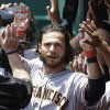 Photo - San Francisco Giants' Brandon Crawford is congratulated in the dugout after hitting a three-run home run off Cincinnati Reds starting pitcher Mike Leake in the fourth inning of a baseball game, Thursday, June 5, 2014, in Cincinnati. (AP Photo/Al Behrman)
