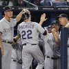 Photo -   Colorado Rockies' Jordan Pacheco (22) is greeted by manager Jim Tracy, left, and and others after hitting a solo home run in the fifth inning of a baseball game against the Atlanta Braves on Tuesday, Sept. 4, 2012, in Atlanta. (AP Photo/John Bazemore)