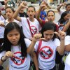 Photo -   Filipino Christian youths flash the thumbs-down signs as they chant