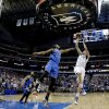 Photo - Dallas Mavericks forward Dirk Nowitzki (41)shoots against Oklahoma City Thunder forward Kevin Durant (35) during overtime of an NBA basketball game Tuesday, March 25, 2014, in Dallas. The Mavericks won 128-119. (AP Photo/LM Otero)