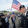 CORRECTS McCARTHY\'S STATE OF RESIDENCE TO RHODE ISLAND - World War II veteran of the U.S. army 29th Infantry Division, Don McCarthy, 90, from Rhode Island, center, arrives for a D-Day commemoration, on Omaha Beach, western France, Friday June 6, 2014. Veterans and Normandy residents are paying tribute to the thousands who gave their lives in the D-Day invasion of Nazi-occupied France 70 years ago. World leaders and dignitaries including President Barack Obama and Queen Elizabeth II will gather to honor the more than 150,000 American, British, Canadian and other Allied D-Day troops who risked and gave their lives to defeat Adolf Hitler\'s Third Reich. (AP Photo/Thibault Camus)