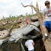 Standing on a fallen tree, Caden Bolles looks over damage to his family\'s home in Little Axe, Oklahoma on Tuesday, May 11, 2010. (AP Photo/The Oklahoman, John Clanton) ORG XMIT: OKOKL104