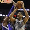 Photo - San Antonio Spurs forward Tim Duncan, right, shoots against Sacramento Kings forward Jason Thompson during the first half of an NBA basketball game, Saturday, Feb. 1, 2014, in San Antonio. (AP Photo/Darren Abate)