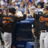 Baltimore Orioles\' Chris Davis, right, is congratulated by Matt Wieters, center, Adam Jones, center left, and Nick Markakis after hitting a three-run homer as Toronto Blue Jays catcher Josh Thole looks on during the sixth inning of a baseball action in Toronto on Friday, June 21, 2013. (AP Photo/The Canadian Press, Chris Young)