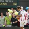 Photo - Roger Federer of Switzerland signs autographs after beating Paolo Lorenzi of Italy during their first round match at the All England Lawn Tennis Championships in Wimbledon, London,  Tuesday, June  24, 2014. (AP Photo/Pavel Golovkin)