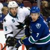 San Jose Sharks\' Jason Demers, left, checks Vancouver Canucks\' David Booth during first period NHL hockey action in Vancouver, British Columbia, on Thursday Nov. 14, 2013. (AP Photo/The Canadian Press, Darryl Dyck)